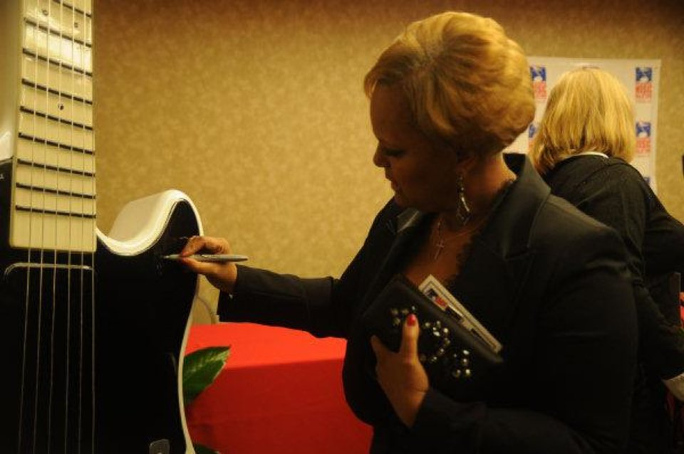 Photo - Regina Tisdale, the wife of former Oklahoma basketball star and jazz musician Wayman Tisdale, signs the Oklahoma Music Hall of Fame guitar Thursday.