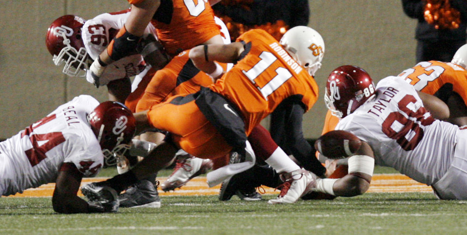 Oklahoma's Jeremy Beal (44) forces a fumble by Oklahoma State's Zac Robinson (11) during the second half of the college football game between the University of Oklahoma Sooners (OU) and Oklahoma State University Cowboys (OSU) at Boone Pickens Stadium on Saturday, Nov. 29, 2008, in Stillwater, Okla. The fumble was returned by OU for a safety. STAFF PHOTO BY CHRIS LANDSBERGER