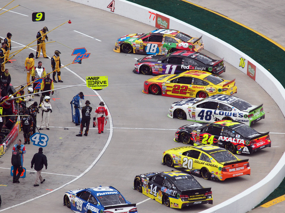 Photo - Cars sit on pit road before the start of a NASCAR Sprint Cup Series auto race at Martinsville Speedway, Sunday, March 30, 2014, in Martinsville, Va (AP Photo/Steve Shappard)