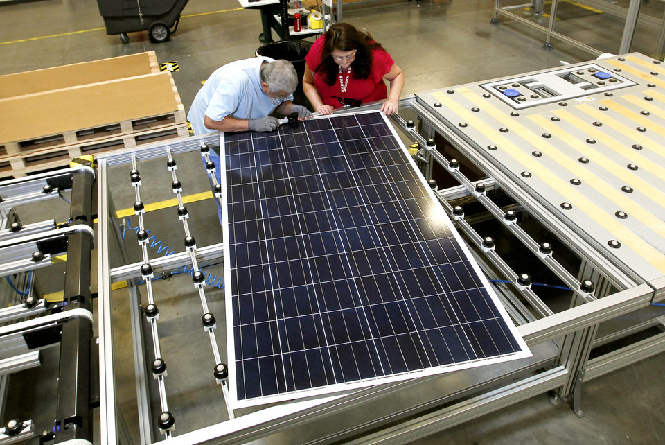 ADVANCE FOR MONDAY, DEC. 3. - In this Sept. 4, 2012 photo, Stacey Rassas, right, a quality control manager at a Suntech Power Holdings Co., a Chinese-owned solar panel manufacturer, examines a solar panel with her co-worker Frank Garcia at a company facility in Goodyear, Ariz. The factory makes solar panels for one of the world's biggest solar manufacturers. (AP Photo/Ross D. Franklin)