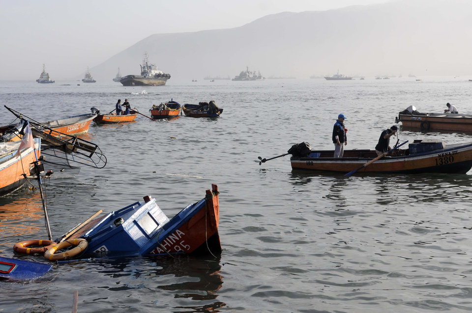 Photo - Fishing boats lie damaged by a small tsunami, in the northern town of Iquique, Chile, after magnitude 8.2 earthqauke struck the northen coast of Chile, Wednesday, April 2, 2014. Authorities lifted tsunami warnings for Chile's long coastline early Wednesday. Six people were crushed to death or suffered fatal heart attacks, a remarkably low toll for such a powerful shift in the Earth's crust. (AP Photo/Cristian Viveros) NO PUBLICAR EN CHILE