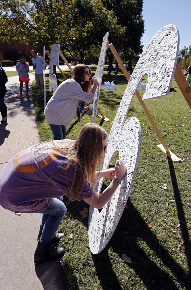 Photo -  University of Oklahoma freshmen Brittany Gaddis and India Maxwell sign numbers representing their proposed graduation date, take a photo and share on social media to earn free homecoming T-shirts at an event on the South Oval.    STEVE SISNEY -