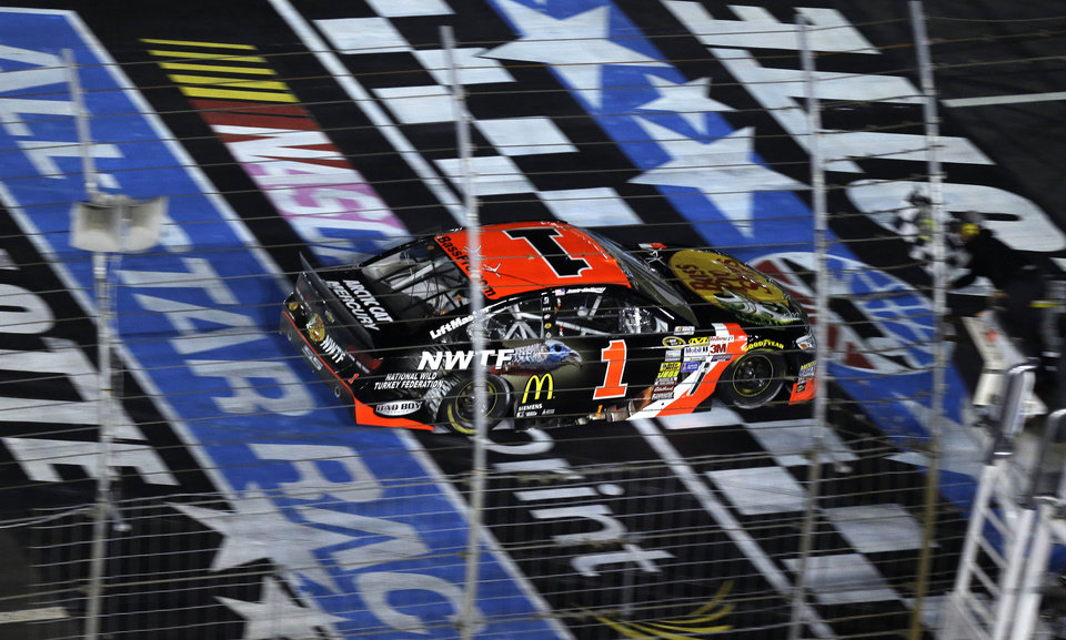 Photo - Jamie McMurray (1) takes the checkered flag to win the NASCAR Sprint All-Star auto race at Charlotte Motor Speedway in Concord, N.C., Saturday, May 17, 2014. (AP Photo/Gerry Broome)