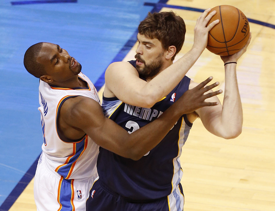 Photo - Oklahoma City's Serge Ibaka (9) defends Memphis' Marc Gasol (33) during Game 1 in the first round of the NBA playoffs between the Oklahoma City Thunder and the Memphis Grizzlies at Chesapeake Energy Arena in Oklahoma City, Saturday, April 19, 2014. Photo by Nate Billings, The Oklahoman