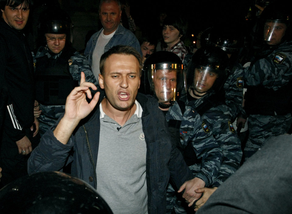 Photo -   Russian riot police officers detain Alexei Navalny, a prominent anti-corruption whistle blower and blogger, center, while he speaks to protesters gathered near the presidential administrations building in downtown Moscow early Tuesday, May 8, 2012, a day after Putin's inauguration. Vladimir Putin took the oath of office in a brief but regal Kremlin ceremony on Monday, while on the streets outside thousands of helmeted riot police prevented hundreds of demonstrators from protesting his return to the presidency. (AP Photo/Alexander Zemlianichenko Jr )