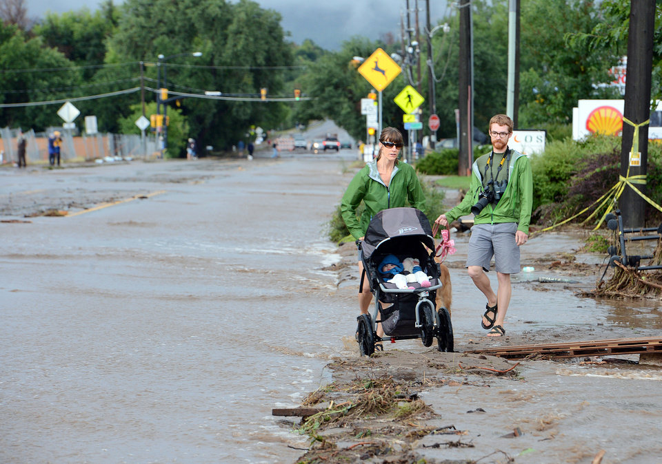 Photo - Kimberly Meyers, her husband, Traeger, and baby Harper, walk along North Broadway in Boulder, Colo.,  to survey the flood damage on Friday, Sept.  13, 2013. Thousands of people in Colorado were ordered to evacuate as water rose to dangerous levels amid a storm system that has been dropping rain for a week. Rescuers struggled to reach dozens of people cut off by flooding in mountain communities. (AP Photo/The Daily Camera, Cliff Grassmick) NO SALES