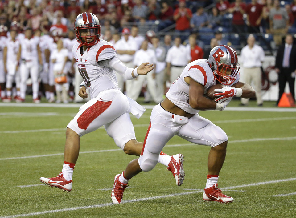 Photo - Rutgers quarterback Gary Nova, left, hands off to running back Paul James, who powered through the line for a touchdown against Washington State in the first half of an NCAA college football game, Thursday, Aug. 28, 2014, in Seattle. (AP Photo/Ted S. Warren)