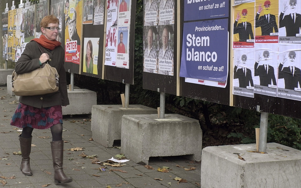 In this photo taken on Monday, Oct. 8, 2012, a woman walks by election campaign posters in Antwerp, Belgium. Historic world port and hip fashionista capital, Antwerp has always lived on the crest of the wave. Now, a separatist Fleming is seeking to make the city his own on Sunday and use it as a base for breaking away from Belgium. Local elections will take place on Sunday, Oct. 14, 2012. Poster reads on second right, \'Vote Blank and annul the election\'. (AP Photo/Virginia Mayo)