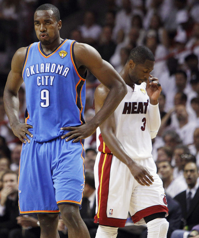Photo -   Oklahoma City Thunder power forward Serge Ibaka (9) from Republic of Congo and Miami Heat shooting guard Dwyane Wade (3) react during the first half at Game 5 of the NBA finals basketball series, Thursday, June 21, 2012, in Miami. (AP Photo/Lynne Sladky)