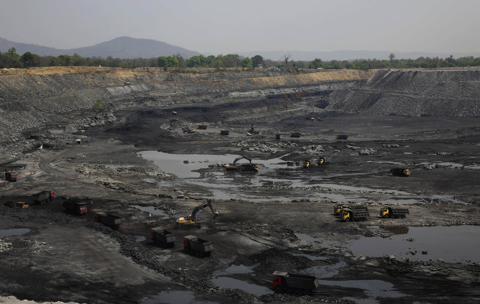 Photo - This April 15, 2014 photo, shows mining in progress at an open coat pit that belongs to Jindal Steel & Power Ltd. at Sarasmal village near the industrial city of Raigarh, in Chhattisgarh state, India. Each morning the ground shakes violently beneath Sarasmal and the neighboring village of Gare as mining crews blast the open coal pit with dynamite, sending clouds of coal dust into the air. (AP Photo/Rafiq Maqbool)