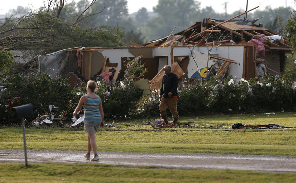 Photo - Residents walk past damaged homes in Carney Okla., on Sunday, May 19, 2013. Photo by Bryan Terry, The Oklahoman