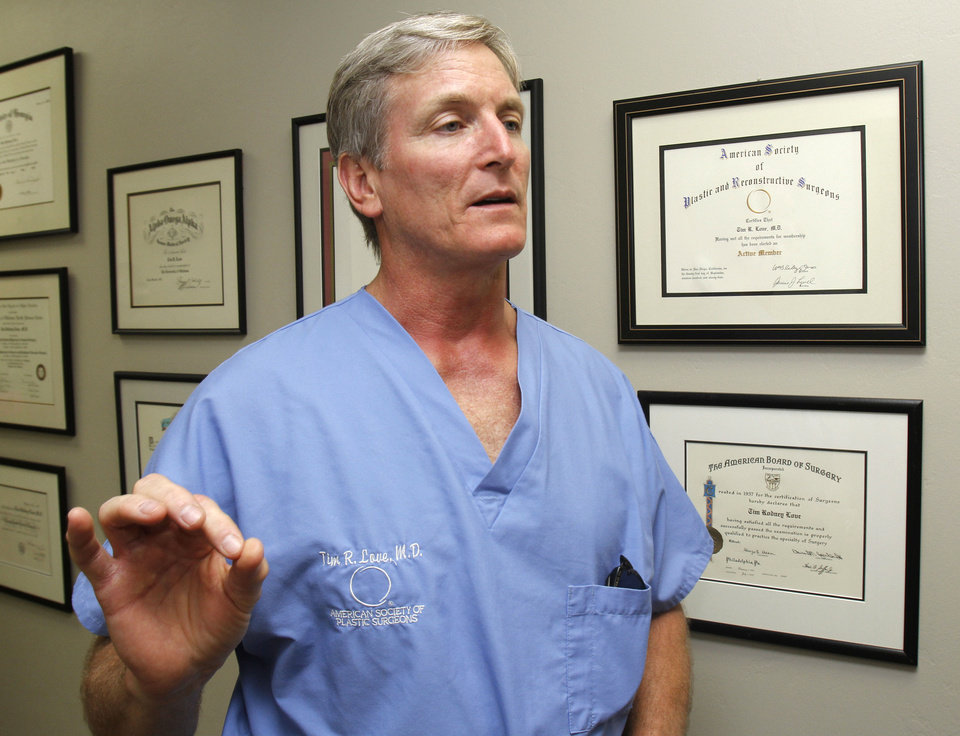 Photo - Plastic surgeon Dr. Tim Love discusses hair follicle transplant procedures Monday at his office in Oklahoma City. Photo by Paul Hellstern, The Oklahoman