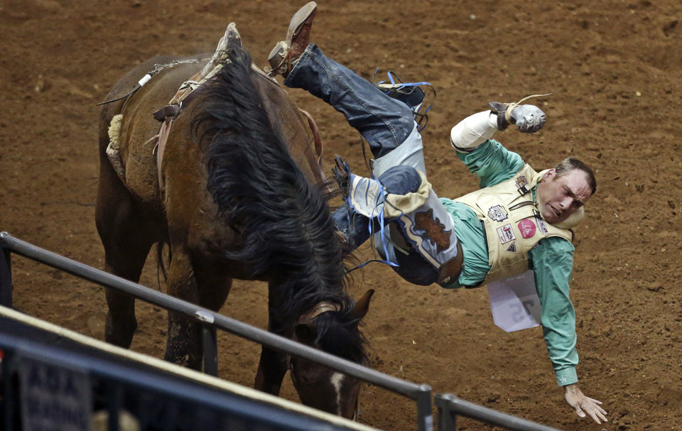 Photo - Wyatt Hancock of Taylor Arz., falls off during the bareback riding competition in the National Circuit Finals Rodeo at the State Fair Arena in Oklahoma City, Thursday, April 4, 2013. Photo by Bryan Terry, The Oklahoman