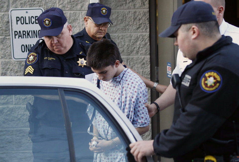 Photo - Alex Hribal, center, the suspect in the stabbings at the Franklin Regional High School near Pittsburgh, is taken from a district magistrate after he was arraigned on charges in the attack on Wednesday, April 9, 2014 in Export, Pa. Authorities say Hribal has been charged after allegedly stabbing and slashing at least 19 people, mostly students, in the crowded halls of his suburban Pittsburgh high school Wednesday. (AP Photo/Keith Srakocic)