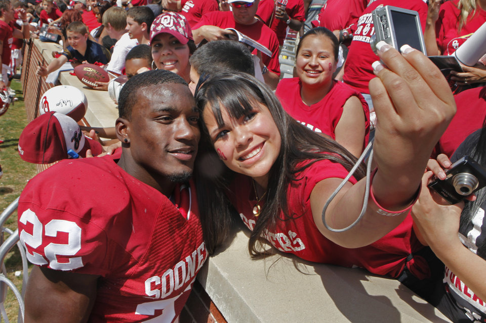 Melody Harjo of Bethany takes her picture with running back Roy Finch (22) after the University of Oklahoma Sooner's (OU) Spring Football game at Gaylord Family-Oklahoma Memorial Stadium on Saturday, April 16, 2011, in Norman, Okla.  