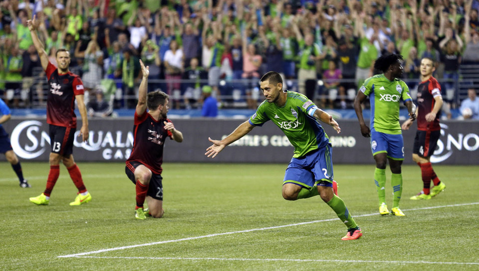 Photo - Seattle Sounders' Clint Dempsey, center, celebrates after scoring a goal against the Portland Timbers, in the second half of an MLS soccer match, Sunday, July 13, 2014, in Seattle. (AP Photo/Ted S. Warren)