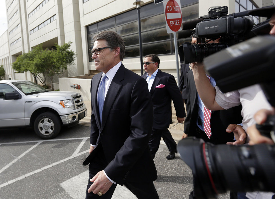 Photo - Texas Gov. Rick Perry, left, leaves the Blackwell Thurman Criminal Justice Center after he was booked, Tuesday, Aug. 19, 2014, in Austin, Texas. Perry was indicted last week on charges of coercion and official oppression for publicly promising to veto $7.5 million for the state public integrity unit run. (AP Photo/Eric Gay)