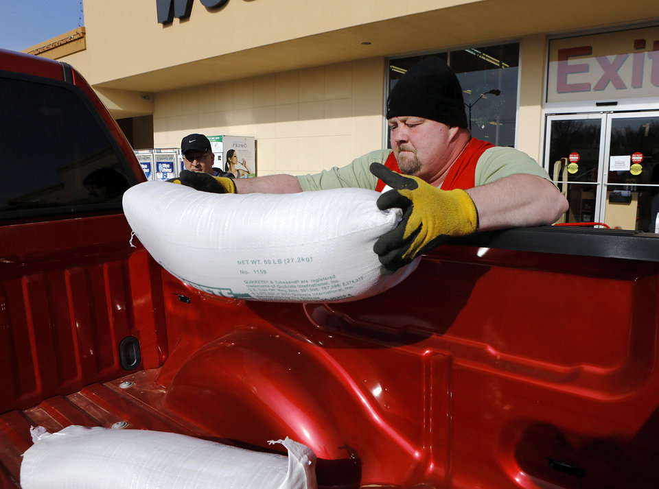 Store employee Brent Gier loads several tubes of sand into the bed of a customer's pickup truck. The customer bought several tubes of sand to provide better traction for his truck. The threat of a severe winter storm, expected to arrive in Oklahoma City on Christmas Day,  ushered a throng of customers into the Westlake Hardware Store, 1509 W. Britton Road,  to purchase snow shovels, ice melt, snow scrapers and tubes filled with sand on Monday, Dec. 24, 2012, Photo by Jim Beckel, The Oklahoman