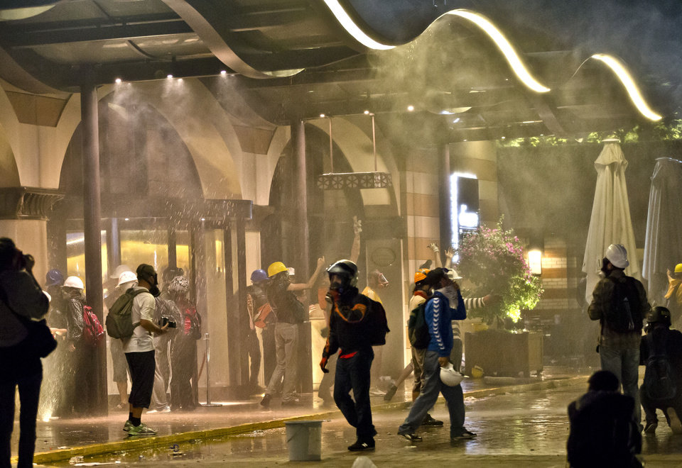 Photo - Protesters are engulfed in tear gas and sprayed by water canons at the entrance of the Divan Hotel in Istanbul, Turkey, Saturday, June 15, 2013 after being chased out of Gezi park.   Protesters set up barricades and plumes of tear gas rose in Istanbul's streets into the early hours Sunday after Turkish riot police firing tear gas and water cannons cleared out the occupation of a park at the center of the strongest challenge to Prime Minister Recep Tayyip Erdogan's 10-year tenure.(AP Photo/Vadim Ghirda)