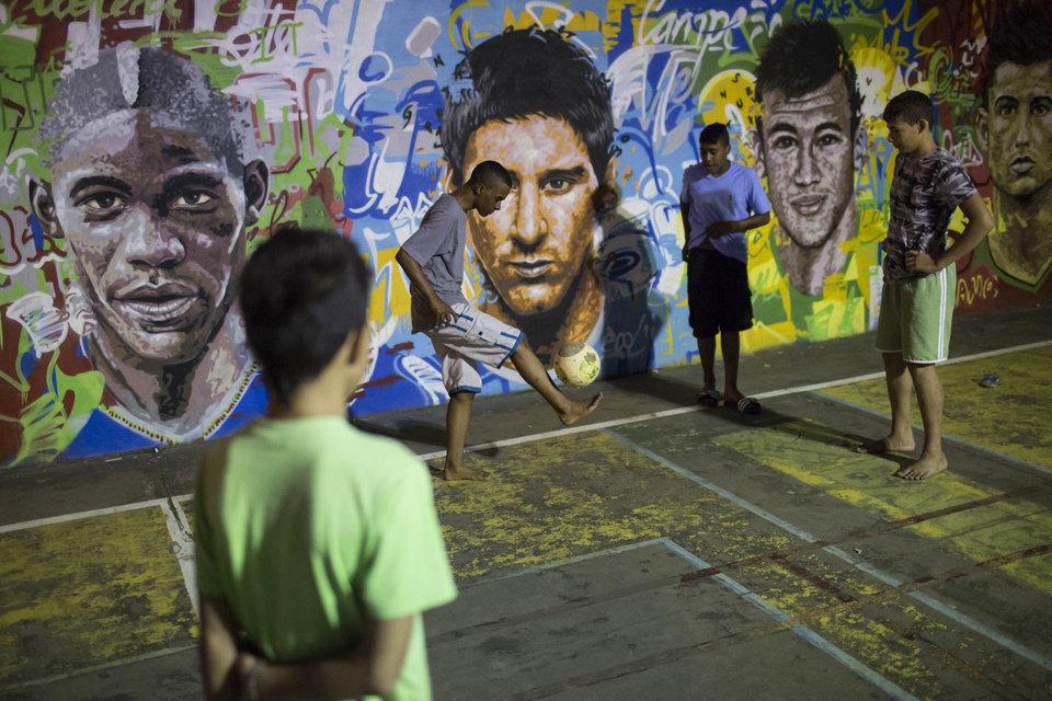 Photo - Boys practice freestyle soccer next to a mural depicting soccer players, from left; Italy's Mario Balotelli, Argentina's Lionel Messi, Brazil's Neymar and Portugal's Cristiano Ronaldo, at a slum in Rio de Janeiro, Brazil, Thursday, June 5, 2014. The Word Cup soccer tournament is set to begin in just a few days, with Brazil and Croatia playing in the opening match on June 12.  (AP Photo/Felipe Dana)