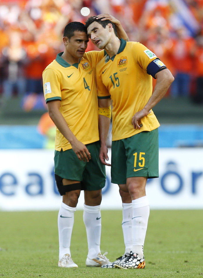Photo - Australia's Tim Cahill, left, consoles teammate Mile Jedinak following the team's 3-2 loss to the Netherlands during the group B World Cup soccer match between Australia and the Netherlands at the Estadio Beira-Rio in Porto Alegre, Brazil, Wednesday, June 18, 2014. (AP Photo/Jon Super)
