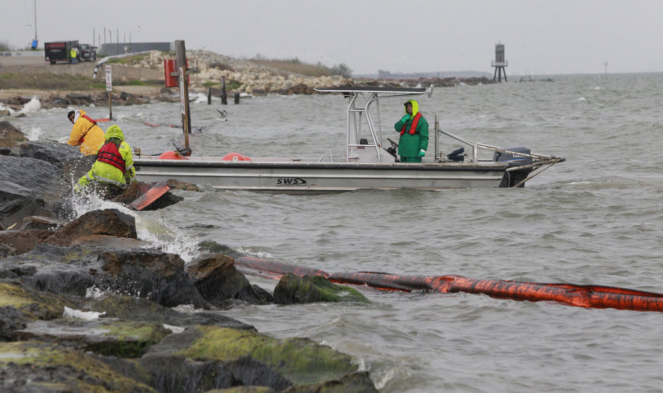 Photo - Workers try to move oil containment boom from the shore area along Boddeker Rd. on the Eastern end of Galveston near the ship channel Sunday, March 23, 2014, in Galveston. (AP Photo/Houston Chronicle, Melissa Phillip)