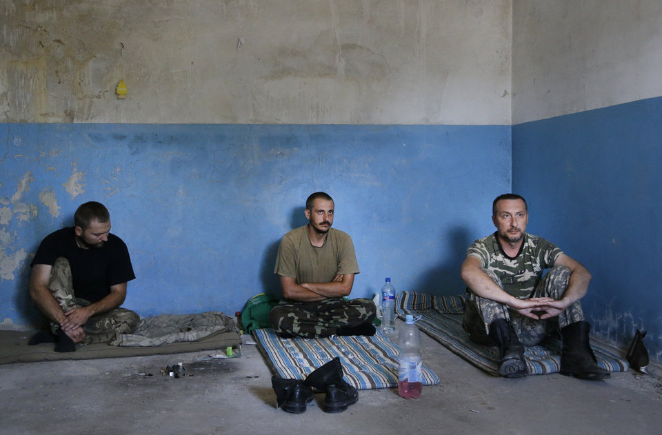 Photo - Captured Ukrainian border guards sit in a  garage at the Novoazovsk border crossing point, in eastern Ukraine, Friday, Aug. 29, 2014. At Novoazovsk, rebel fighters looked to be in firm control, well-equipped and relaxed. At least half a dozen tanks were seen on roads around the town, although the total number at the rebels' disposal is believed to be much greater. Novoazovsk fell swiftly to the rebels Wednesday after being pounded by shelling.(AP Photo/Sergei Grits)