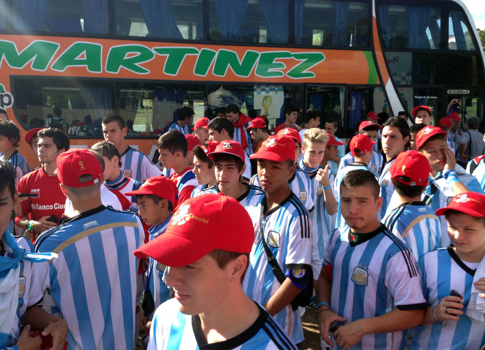 Photo - Youth from the Renato Cesarini football academy arrive to the base used by Argentina's soccer team during the World Cup soccer tournament in Belo Horizonte, Brazil, Tuesday, June 17, 2014.  They traveled for 50 hours by bus from Lionel Messi's hometown, Rosario, hoping to catch a glimpse of the Argentina star. (AP Photo/Karl Ritter)