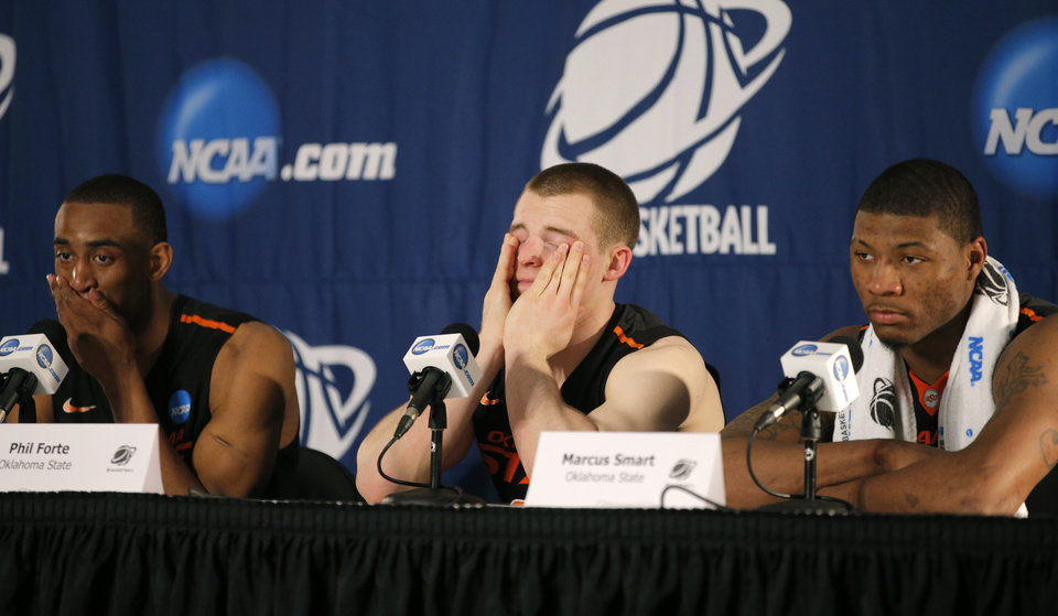 Photo - Oklahoma State's Markel Brown, left, Phil Forte, and Marus Smart answer questions during a press conference following their  second round game of the NCAA men's college basketball tournament at Viejas Arena in San Diego, between Oklahoma State and Gonzaga Friday, March 21, 2014. Gonzaga won 85-77. Photo by Bryan Terry, The Oklahoman
