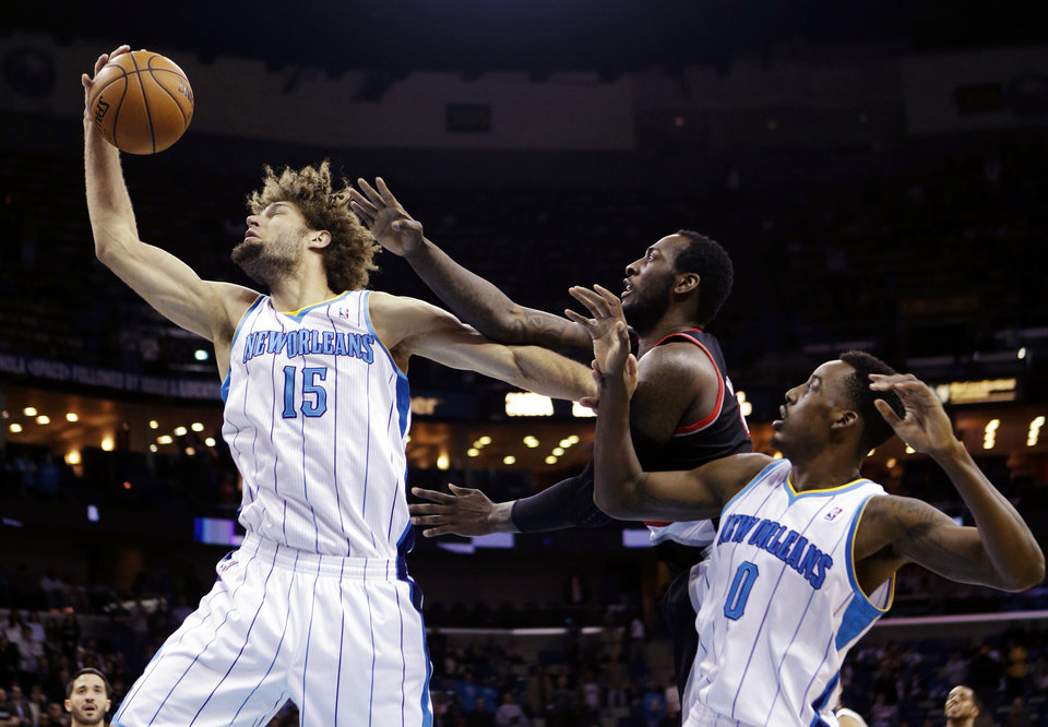 Photo - New Orleans Hornets center Robin Lopez (15) pulls in a rebound in front of Portland Trail Blazers center J.J. Hickson, center, and Hornets forward Al-Farouq Aminu (0) in the first half of an NBA basketball game in New Orleans, Wednesday, Feb. 13, 2013. (AP Photo/Gerald Herbert)