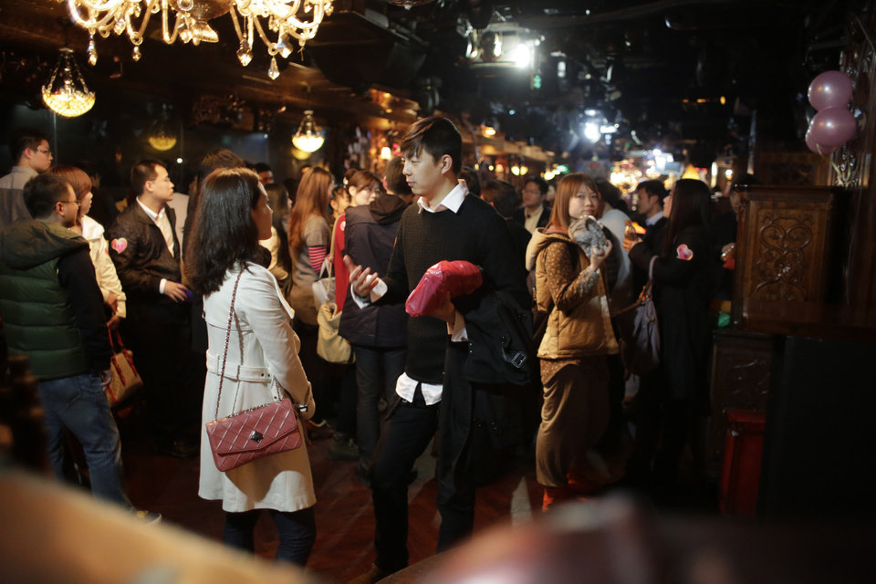 "A man and woman participants who are singles chat during a matchmaking party organized by one of the biggest Chinese matchmaking websites in Shanghai, China on Sunday Nov. 11, 2012. Singles Day was begun by Chinese college students in the 1990s as a version of Valentine's Day for people without romantic partners. The timing was based on the date Nov. 11, or ""11.11"" � four singles. Unattached young people would treat each other to dinner or give gifts to woo that special someone and end their single status. (AP Photo/Eugene Hoshiko)"