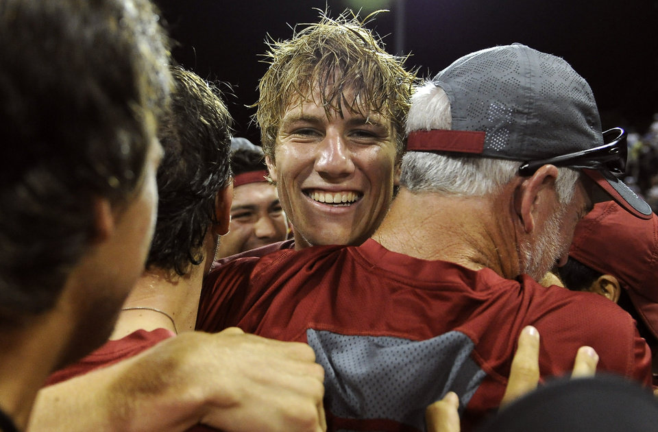 Photo - USC's Max de Vroome, center, hugs coach Peter Smith after defeating Oklahoma's Andrew Harris to take the NCAA Division I tennis championships, Tuesday, May 20, 2014, in Athens, Ga. (AP Photo/David Tulis)