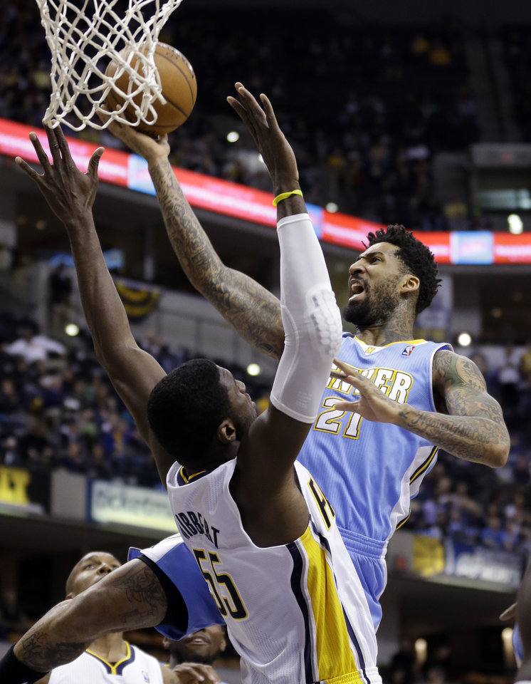 Photo - Denver Nuggets forward Wilson Chandler, right, gets a basket over Indiana Pacers center Roy Hibbert in the first half of an NBA basketball game in Indianapolis, Monday, Feb. 10, 2014. (AP Photo/Michael Conroy)