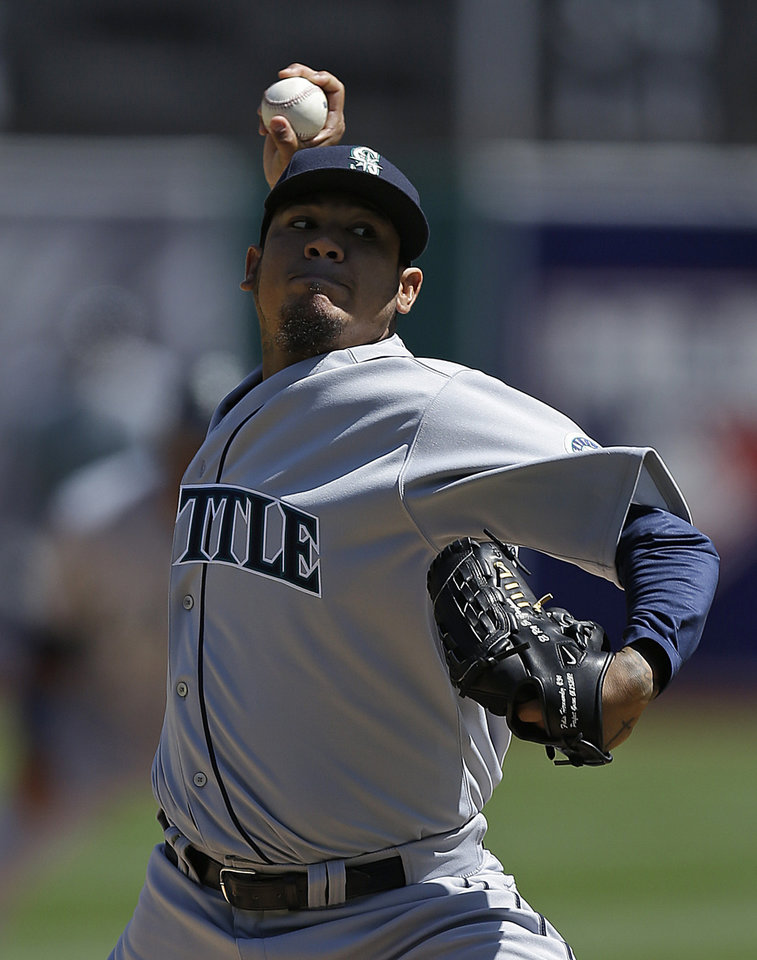 Photo - Seattle Mariners' Felix Hernandez works against the Oakland Athletics in the first inning of a baseball game on Saturday, April 5, 2014, in Oakland, Calif. (AP Photo/Ben Margot)