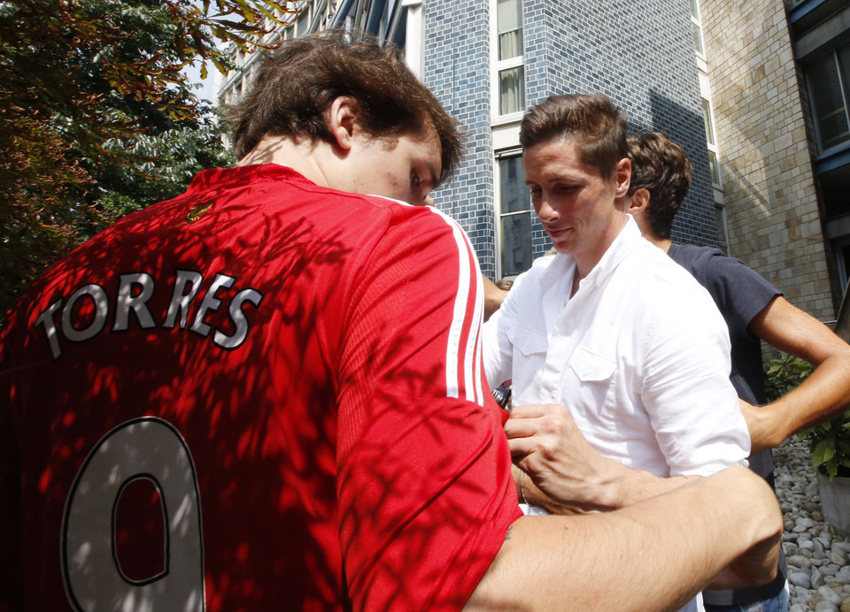 Photo - Spanish striker Fernando Torres, right, signs autographs to AC Milan supporters as he arrives at the