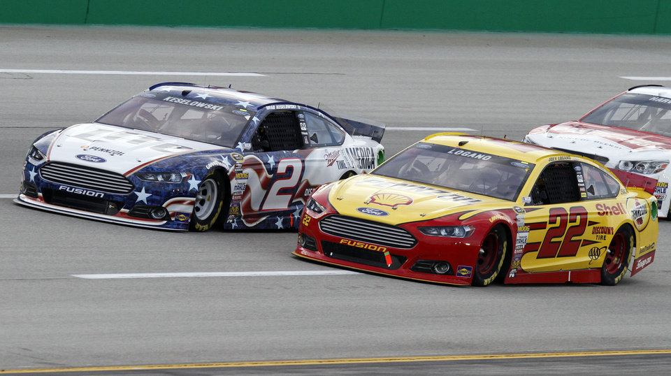 Photo - Brad Keselowski (2) and Joey Logano (22) vie for the lead in the NASCAR Sprint Cup series auto race Saturday, June  28, 2014, at Kentucky Speedway in Sparta, Ky. (AP Photo/James Crisp)
