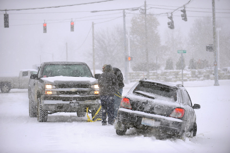 Photo - A good samaritan helps pull a motorist from the ditch on 32nd Street in Paducah, Ky., as snow fall Friday, Dec. 6, 2013. A winter mix of precipitation will continue through the day. A second winter storm is forecasted for Saturday night. (AP Photo/Stephen Lance Dennee)
