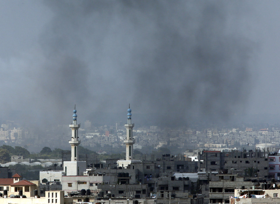 Photo - Smoke rises after an Israeli missile strike in Gaza City, northern Gaza Strip, Friday, July 18, 2014. Israel intensified its 11-day campaign against Hamas by sending in tanks and troops late Thursday after becoming increasingly exasperated with unrelenting rocket fire from Gaza on its cities, especially following Hamas' rejection of an Egyptian cease-fire plan earlier in the week.(AP Photo/Lefteris Pitarakis)