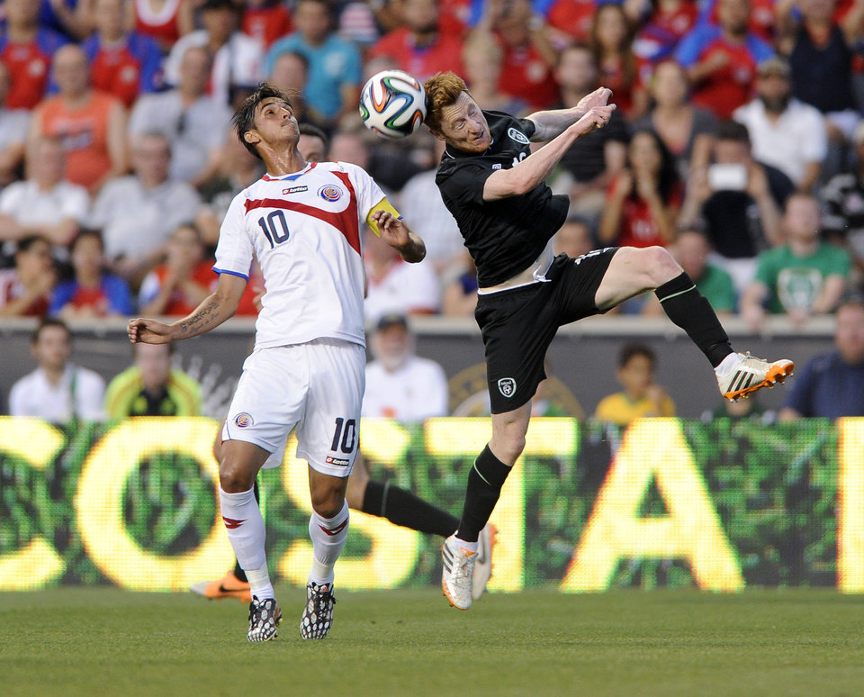 Photo - Ireland's Stephen Quinn, right, heads the ball past Costa Rica's Bryan Ruiz during the first half of an international friendly soccer match on Friday, June 6, 2014, in Chester, Pa. (AP Photo/Michael Perez)