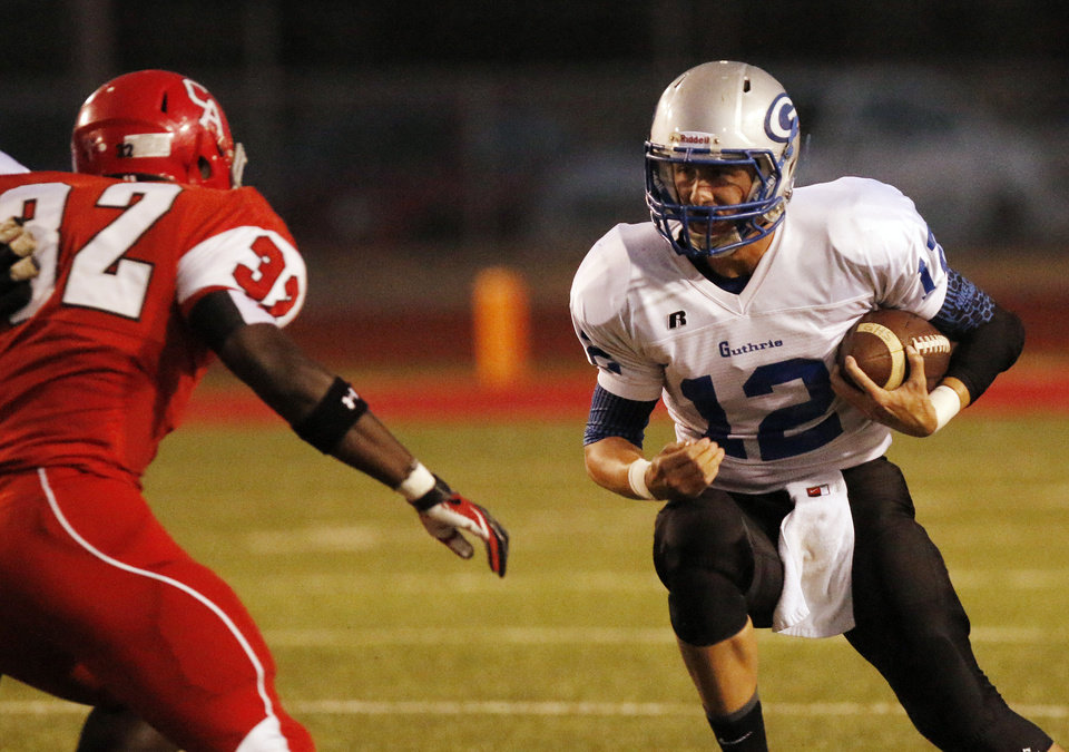 Photo -  Guthrie's Reed Roberts runs toward Carl Albert's Nate Christmon during the high school football game between Guthrie at Carl Albert in Midwest City, Friday, October 11, 2013.  Photo by Doug Hoke, The Oklahoman