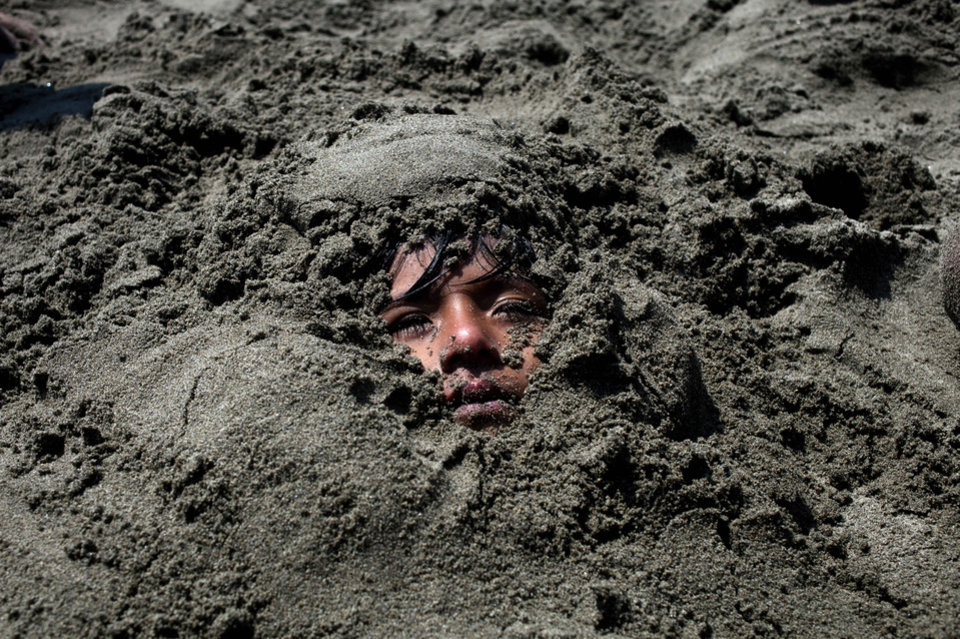 Photo - In this Jan. 24, 2013 photo,  Maria Kalet, 6, lies buried in the sand at Agua Dulce beach in Lima, Peru. While Lima's elite spends its summer weekends in gate beach enclaves south of the Peruvian capital, the working class jams by the thousands on a single municipal beach of grayish-brown sands and gentle waves. Until the mid-20th century, Lima's lower classes couldn't afford beach-going, said Juan Pacheco, a historian of the city. Road-building to the coast solved that, and the rich began to largely abandon Lima's beaches to the poorer set. (AP Photo/Rodrigo Abd)
