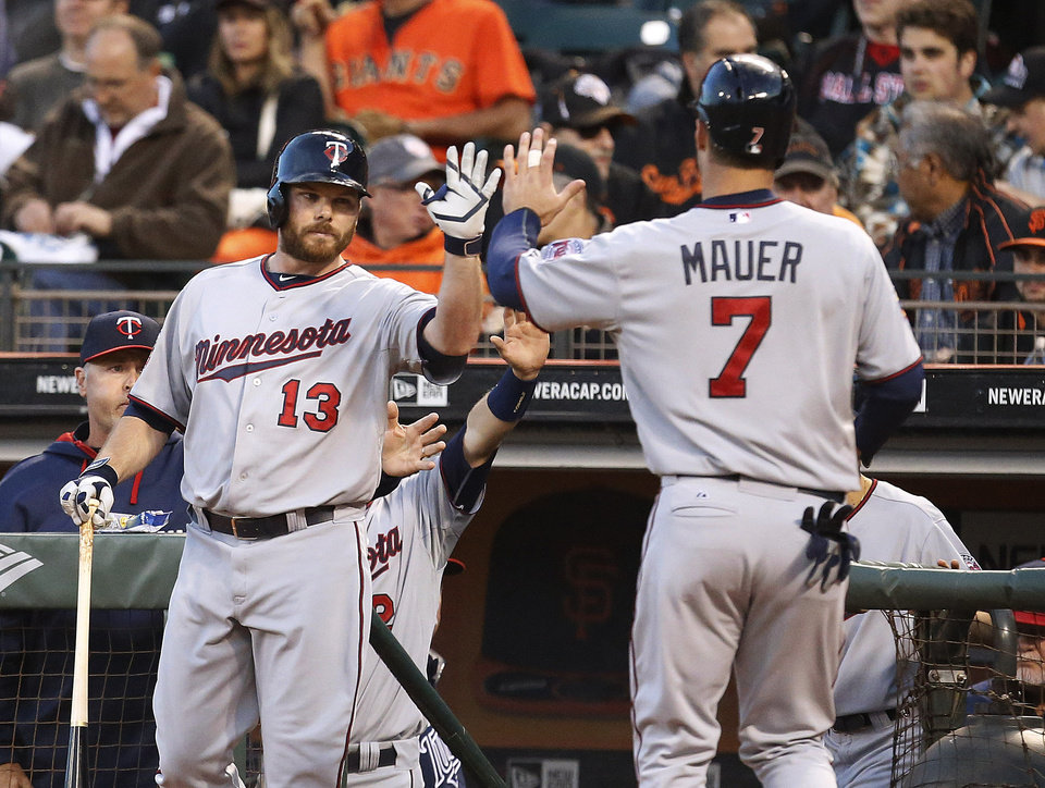 Photo - Minnesota Twins first baseman Joe Mauer (7) is congratulated by teammate Jason Kubel (13) after scoring a run against the San Francisco Giants in the third inning of a baseball game Friday, May 23, 2014, in San Francisco. (AP Photo/Tony Avelar)