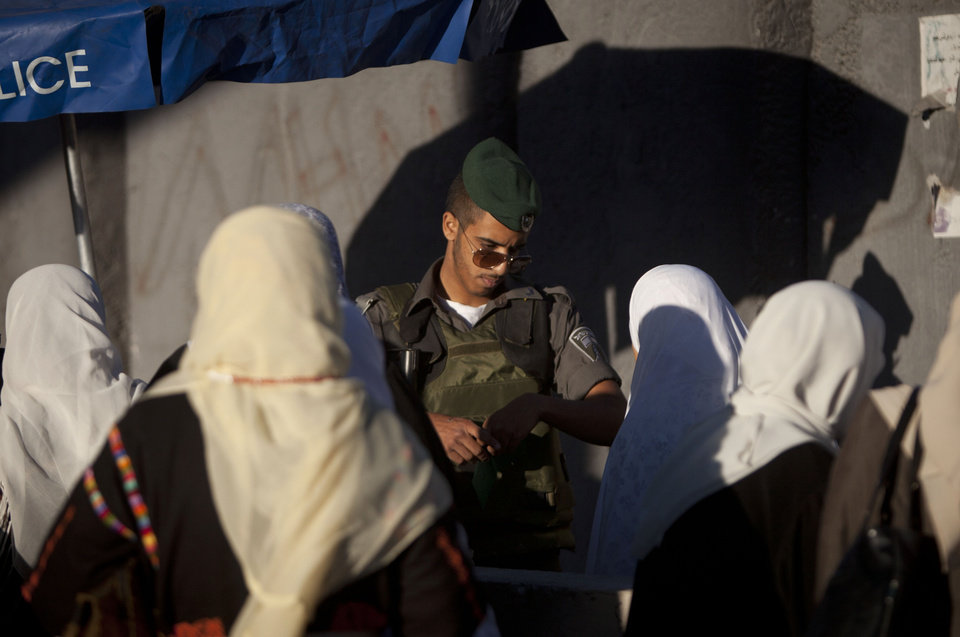 Photo - An Israeli border police officer checks documents of Palestinian women on their way to pray at the Al-Aqsa Mosque in Jerusalem during the Muslim holy month of Ramadan at the Qalandia checkpoint, between the West Bank city of Ramallah and Jerusalem, Friday, July 11, 2014. (AP Photo/Majdi Mohammed)