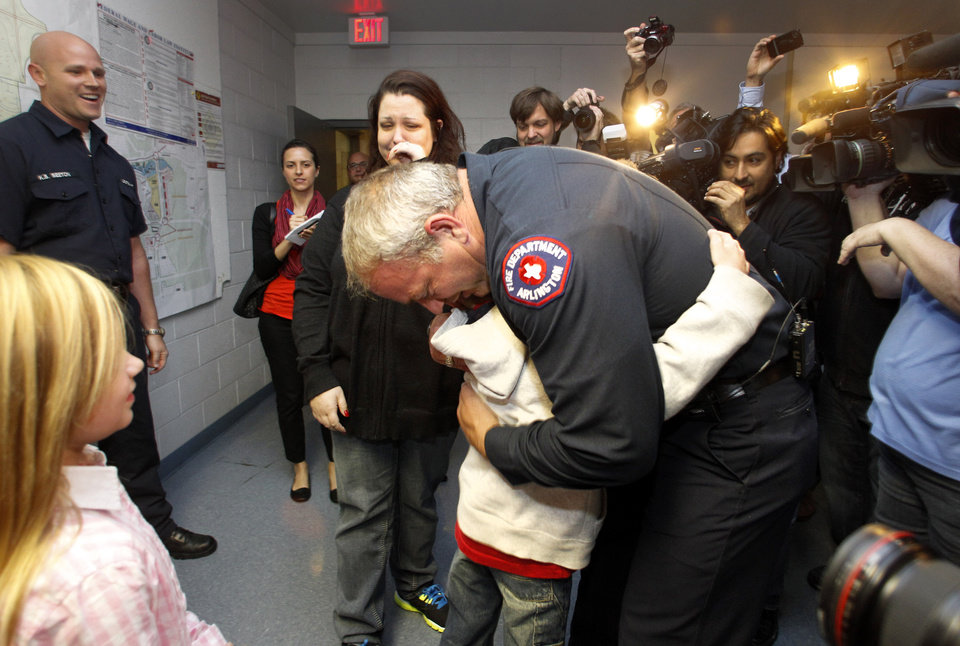 Photo -   Rebecca Quintanilla, center left, wipes tears from her face as her adopted son Koregan, 10, hugs Arlington Fire Fighter Wesley Keck, center right, as the two meet Thursday, Nov. 15, 2012, in Arlington, Texas. A Texas boy abandoned at a fire station as an infant got his wish for his 10th birthday: to meet the firefighter who saved him. On Thursday evening, the boy was to celebrate his recent birthday by meeting Arlington firefighter Wesley Keck, riding on a fire truck and touring the station. (AP Photo/Tony Gutierrez)