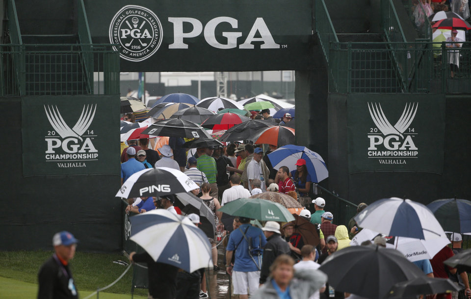 Photo - Golf fans walk off the first hole during a rain delay in the final round of the PGA Championship golf tournament at Valhalla Golf Club on Sunday, Aug. 10, 2014, in Louisville, Ky. (AP Photo/Mike Groll)