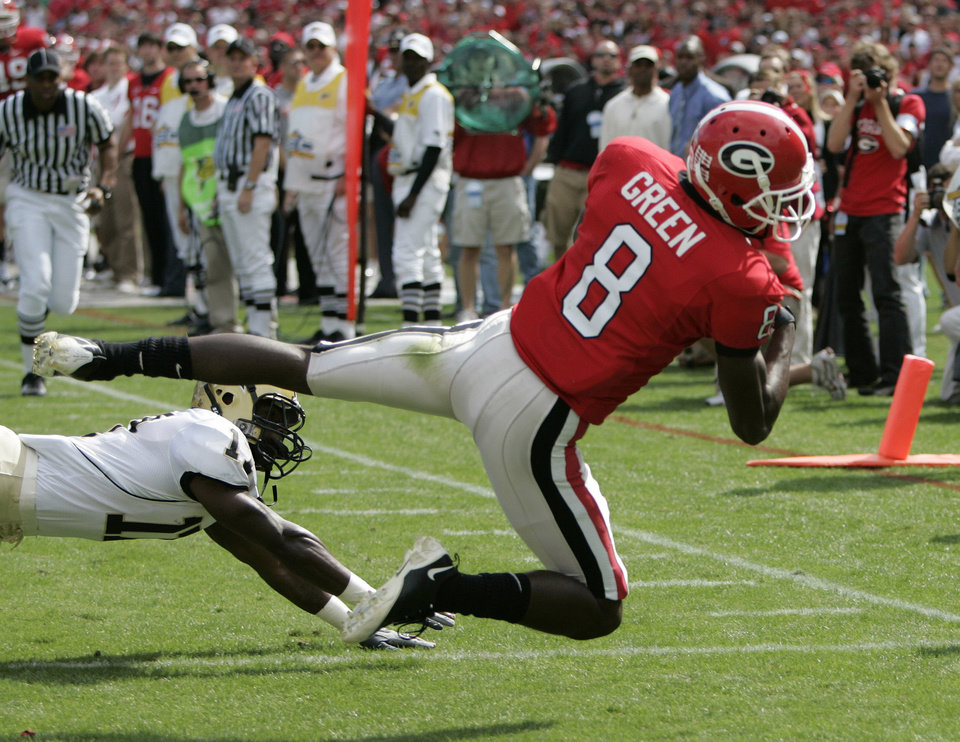 Photo - COLLEGE FOOTBALL: Georgia receiver A.J. Green (8) hauls in a pass from Matthew Stafford for a touchdown as Vanderbilt's D.J. Moore defends during the first quarter of an NCAA college football game in Athens, Ga., Saturday, Oct. 18, 2008. Georgia won 24-14. (AP Photo/John Bazemore)