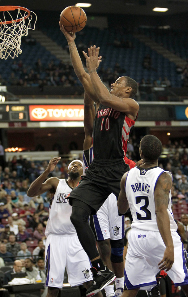 Toronto Raptors guard DeMar DeRozan, center, goes to the basket between  Sacramento Kings' John Salmons, left, and Aaron Brooks  during the first quarter of an NBA basketball game in Sacramento, Calif., Wednesday, Dec. 5, 2012. (AP Photo/Rich Pedroncelli)