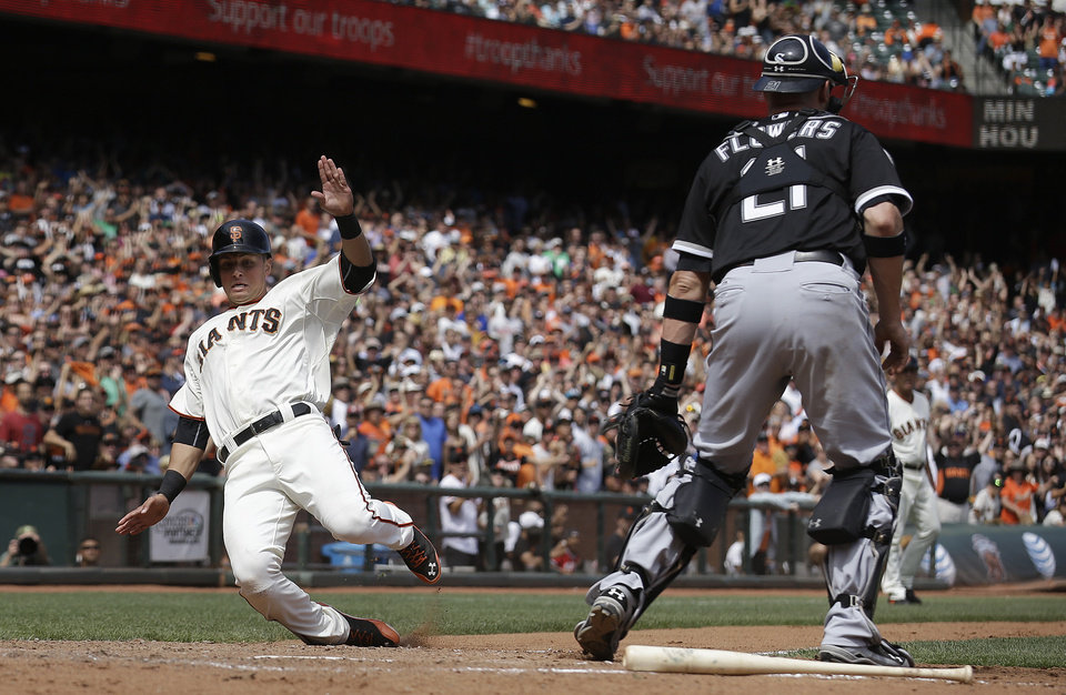 Photo - San Francisco Giants' Joe Panik, left, scores past Chicago White Sox catcher Tyler Flowers (21) on Angel Pagan's single during the seventh inning of a baseball game in San Francisco, Wednesday, Aug. 13, 2014. (AP Photo/Jeff Chiu)