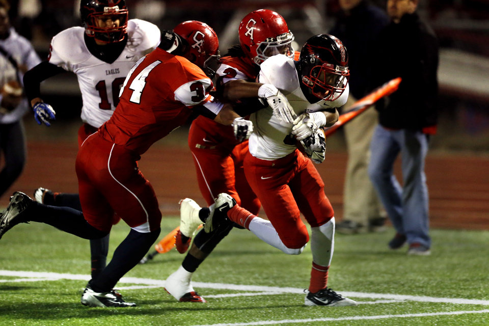 Photo - Del City's Zack Jones carries inside the five yard line on a long run brought down by Carl Albert's Dustin Blasingame, left, and Dillon Lohr as the Titans play the Del City Eagles on Friday, Nov. 15, 2013  in Midwest City, Okla. Photo by Steve Sisney, The Oklahoman