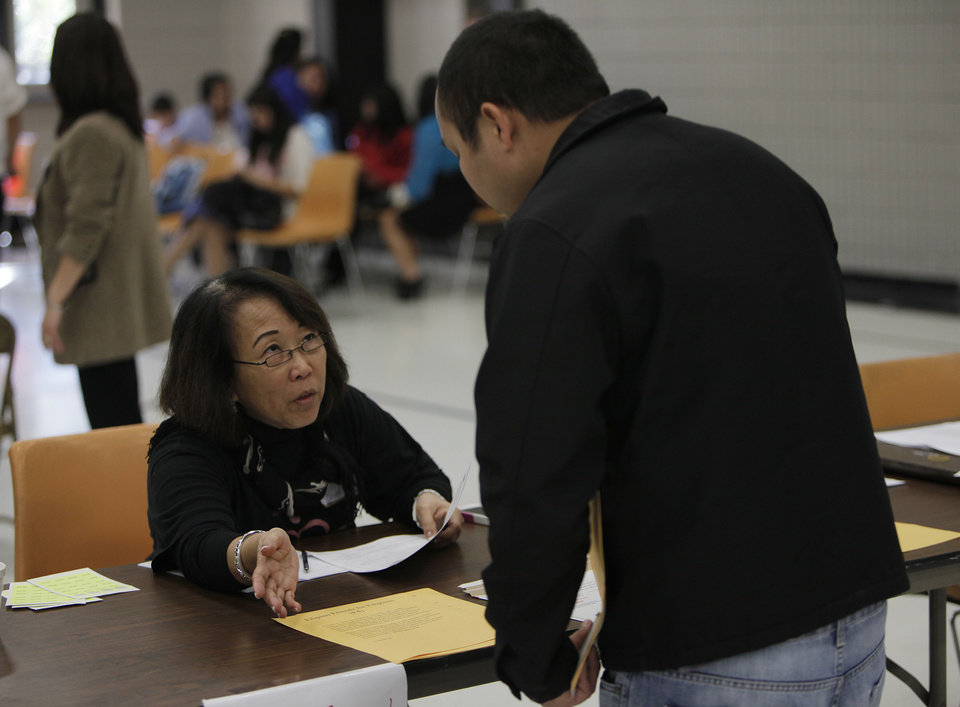 Beth Linga helps Edward Linga apply for a new passport at St. Eugene Catholic Church in Oklahoma City.  Photo by Garett Fisbeck, The Oklahoman <strong>Garett Fisbeck - Garett Fisbeck</strong>